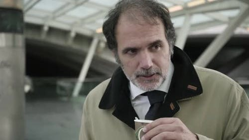 Mature Business Man in Tie and Overcoat Drinking Takeaway Coffee