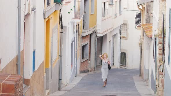 Thumbnail for Woman Tourist Admiring the Ancient Street in the Old Town in Spain. It Goes Down the Narrow Street