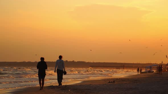 Colorful sea beach sunset. People walking during beautiful colorful sunset at the sea