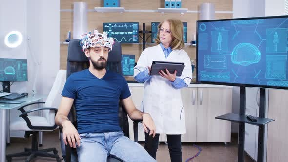 Female Doctor Checking the Brain Activity of Male Patient