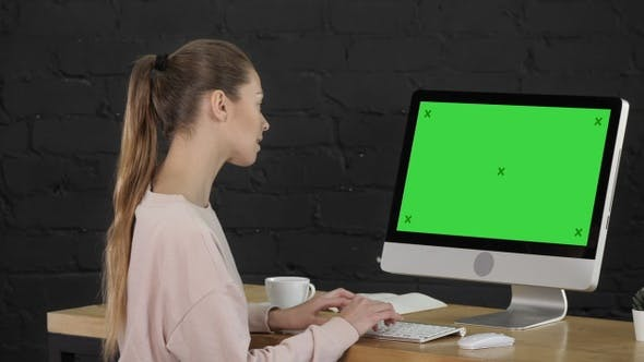 Cover Image for Young woman in office working on desktop computer. Green