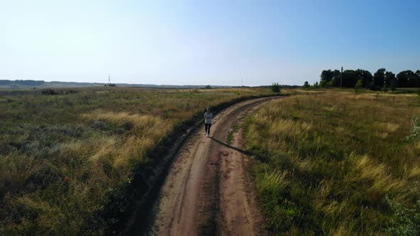 Thumbnail for Drone Flies Over Jogger Running on Byroad Rural Area
