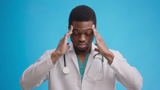 Thumbnail for Professional Medical Doctor Suffering From Acute Migraine Attack, Blue Studio Background