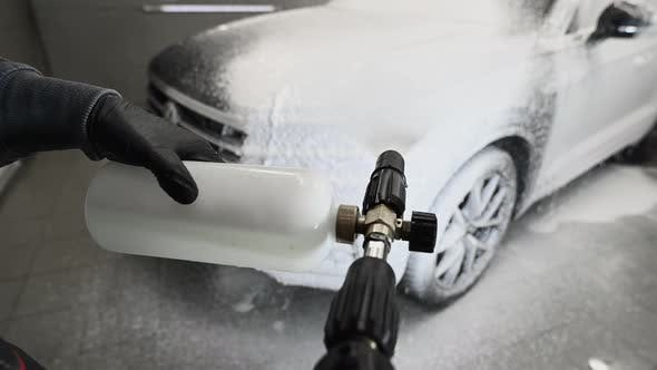 Man Covering a Car with Foam Using High Pressure Washer