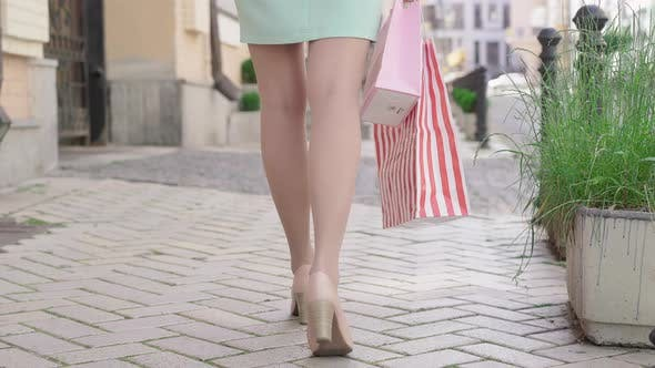 Camera Follows Slim Legs of Elegant Caucasian Woman in Dress and High-heels Walking Along the Street