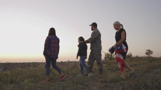 Thumbnail for Soldier and His Family Walking on a Meadow