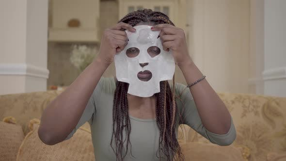 Thumbnail for Portrait of Pretty African American Woman Putting Moisturizing Facial Mask on Her Face on the Coach