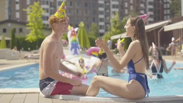 Side View of Positive Young Man and Woman Blowing Party Whistles and Giving High Five As Friends