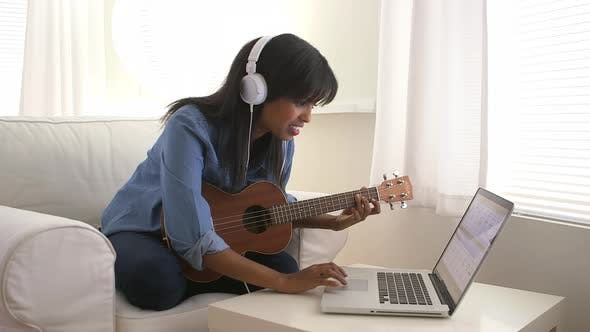 Thumbnail for Black girl recording song on ukulele with laptop