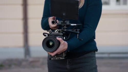 Female Film Maker Using Film Camera In Street
