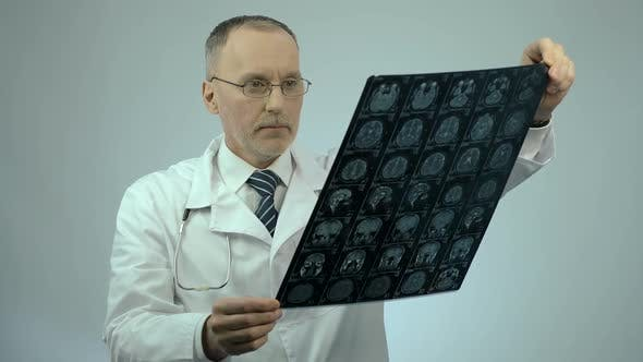 Thumbnail for Neurosurgeon Checking MRI Brain Image, Looking at Camera, Health Care Services
