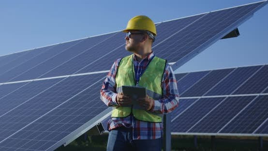 Thumbnail for Adult Engineer Using Tablet Working Among Solar Panels