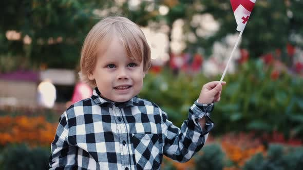 Thumbnail for Little Boy in Checkered Shirt Holding Georgian Flag