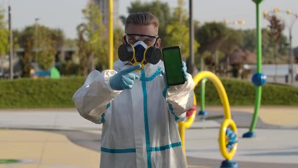 Thumbnail for Portrait Young Man in a Protective Suit, Glasses, a Respirator and Gloves Holds a Smartphone with