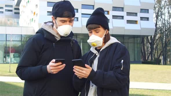 Thumbnail for Young Couple of Millenials on Street in Respiratory Mask and Showing News