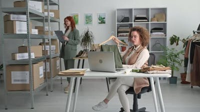 Clothing Store Young Charming Female Saleswoman Sells Clothes Online to Customer Using Laptop and