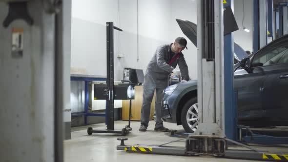 Thumbnail for Adult Professional Auto Mechanic Adjusting Lightning Equipment in Auto Repair Shop. Caucasian Man