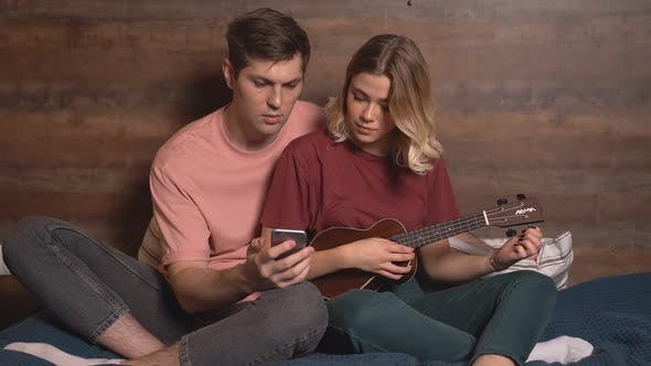 Young Couple Sitting at Home Watching Guitar Lessons on Their Smartphone. A Couple in Love in Casual