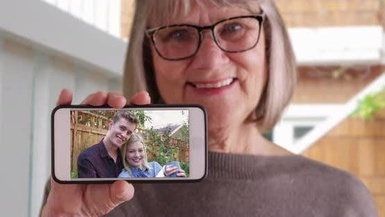 Thumbnail for Gentle elderly woman showing picture of her daughter with her boyfriend on phone