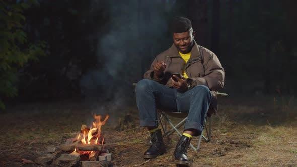 Black Hiker Checking Cellphone Near Campfire
