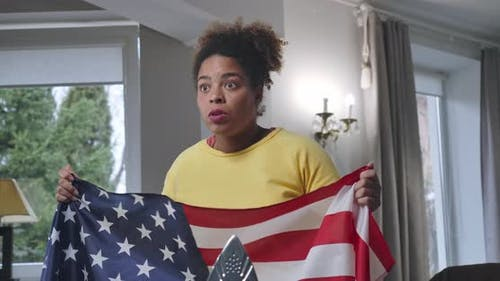 Middle Shot of Enthusiastic African American Woman Holding USA Flag Cheering for Football Team at