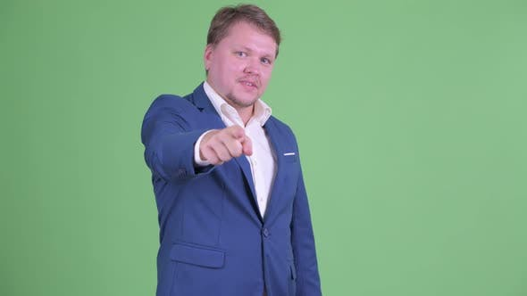 Thumbnail for Happy Overweight Bearded Businessman Pointing at Camera