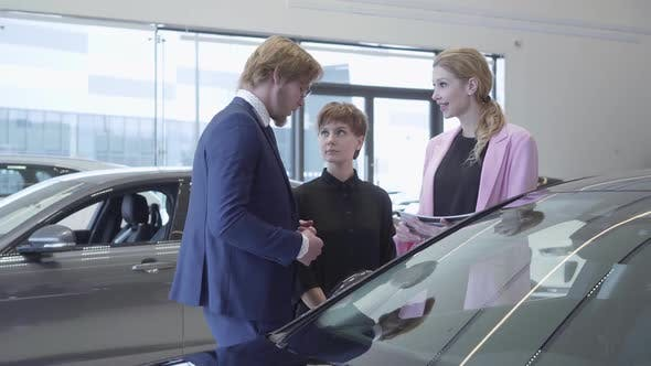 Thumbnail for Bearded Salesman in a Business Suit Tells Two Young Girls Information About a New Car