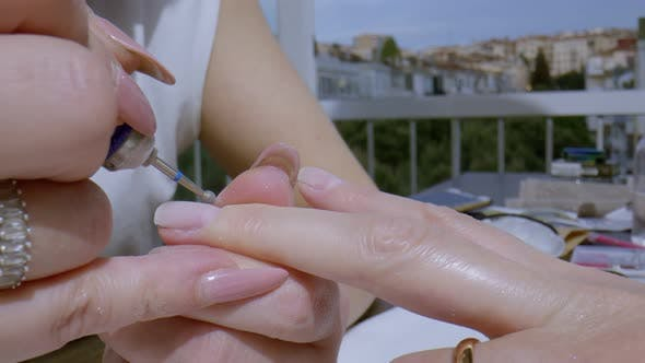 Manicurist Removing Cuticle.