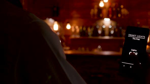 Cover Image for Dolly Shot of Waiter Using His Phone To Turn on the Lights in the Restaurant