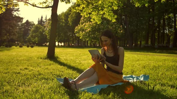 Thumbnail for Cheerful, Young Woman Browsing Her Tablet in the Park.