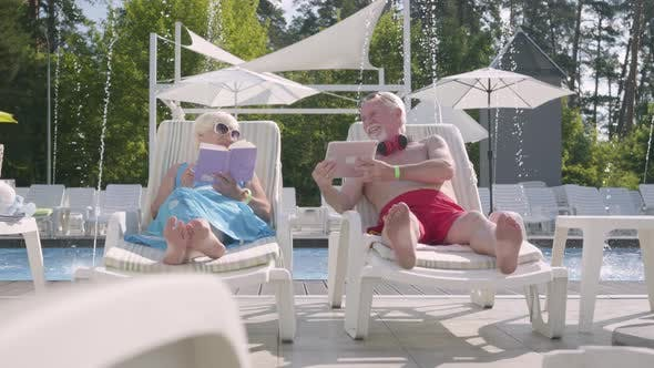 Thumbnail for Adorable Positive Couple Lying on Sunbeds Near the Pool. The Woman Reading the Book