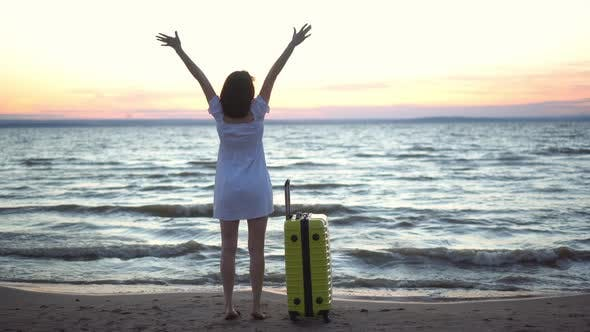 Thumbnail for Young Woman with a Yellow Suitcase on the Beach By the Sea. A Girl in a White Dress Looks at the