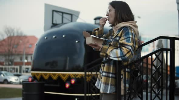 Woman eats street food from a food truck
