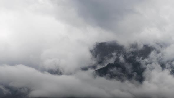 Thumbnail for Close Up of Clouds Flowing Around Mountain Peaks Time Lapse