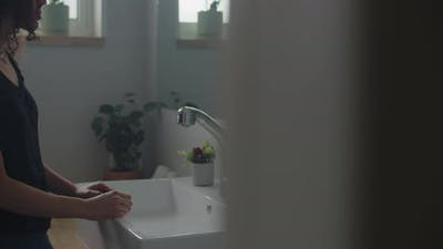 Woman leaning on the bathroom sink