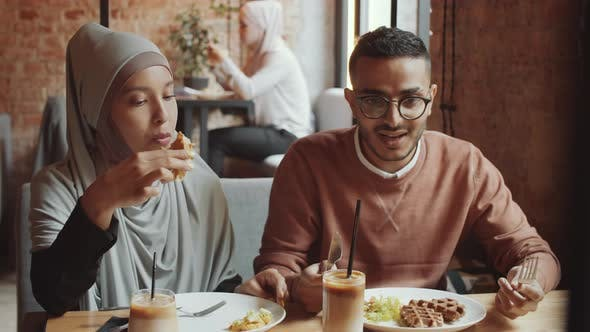 Thumbnail for Muslim Couple Eating Lunch and Chatting in Cafe