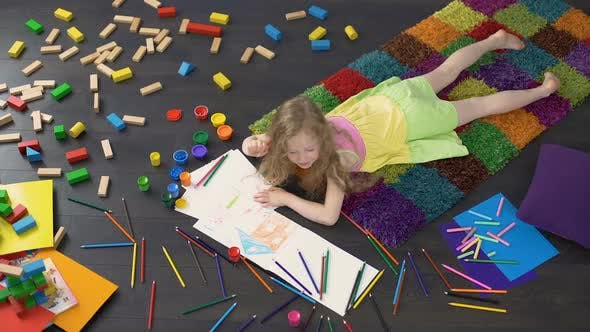 Cover Image for Little Curly Girl Drawing with Color Pencils on The Floor at Home Childhood