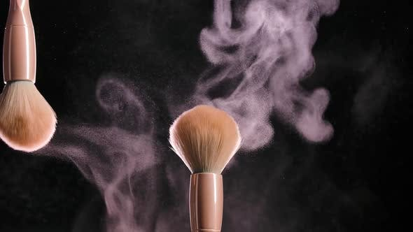 Two Soft Cosmetic Brushes Release a Cloud of Powder Particles in Contact with Each Other