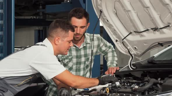 Thumbnail for Car Service Mechanic Repairing Automobile While Talking To the Customer