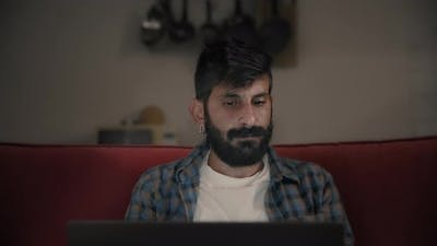 A man finishes working on a laptop
