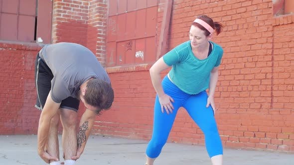 Thumbnail for A couple working out and stretching together in an urban environment