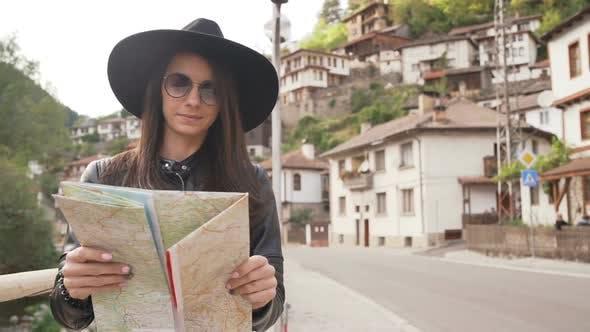 Travel Girl with Touristic Map in Shiroka Laka, Bulgaria. Happy Women Enjoy Bulgarian Vacation