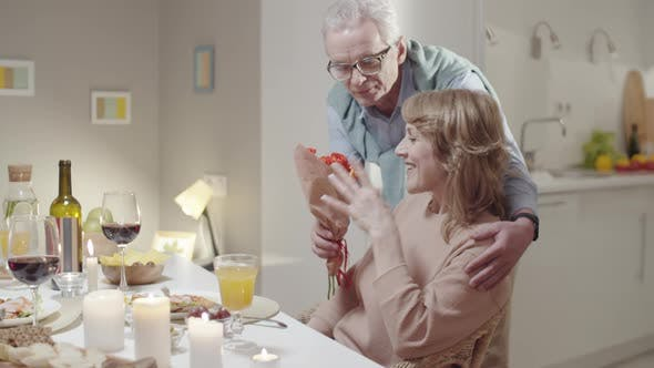 Senior Man Giving Flowers to Wife at Romantic Dinner