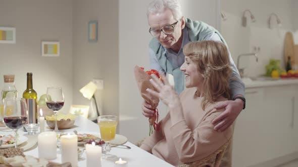 Thumbnail for Senior Man Giving Flowers to Wife at Romantic Dinner