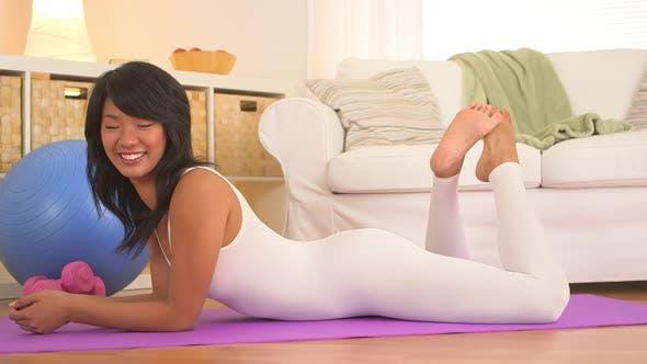 Asian woman lying on yoga mat in living room