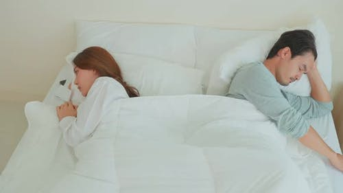Asian young couple lying down on bed feel heartbroken with painful after fight argument in bedroom.