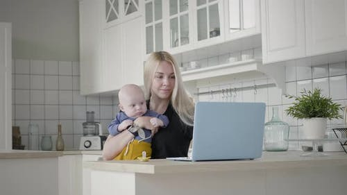 Mother Taking Care Her Baby While Working At Home