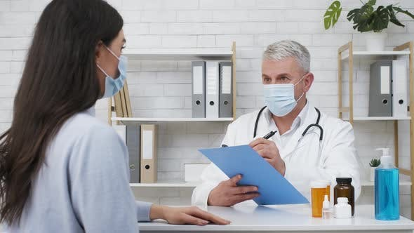 Doctor Consulting Sick Female Patient About Treatment In Clinic Office