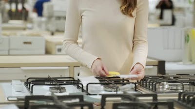 Woman Choosing New Gas Stove in Home Appliances Store