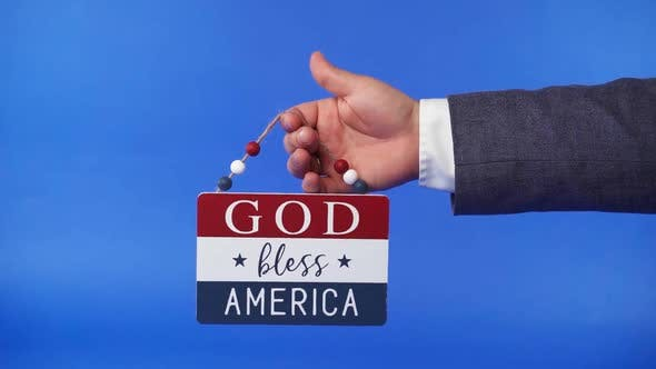 Hand Holding A Patriotic Religious Sign